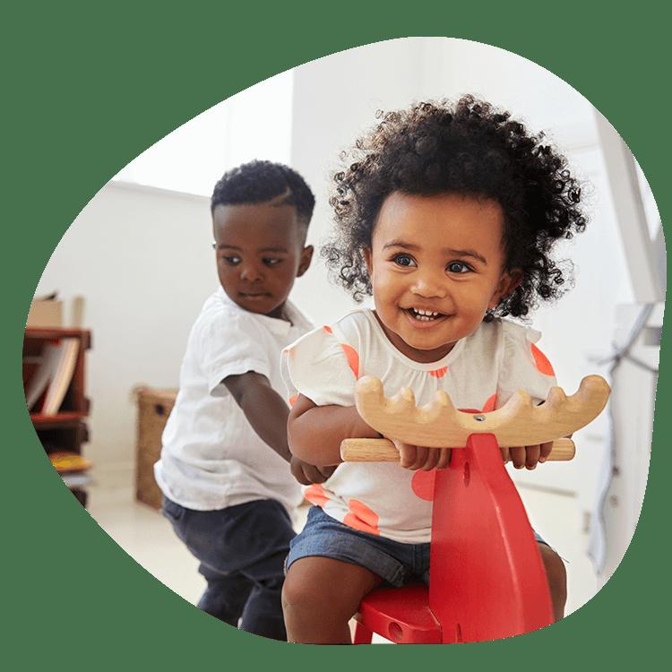 Twee spelende kindjes op een hobbelpaard